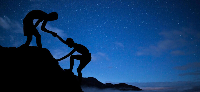 One person helps another climb a mountain